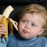 маленький мальчик ест банан